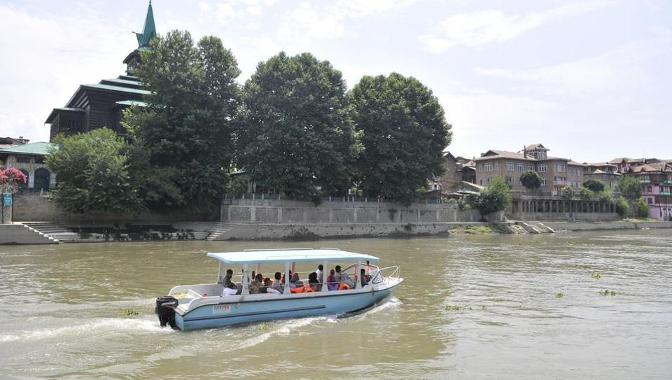 A motor-boat, issued by the government for trial run of waterway transportation on the Jhelum, moves past the Shah-e-Hamadan shrine in Srinagar .(Waseem Andrabi / HT Photo)