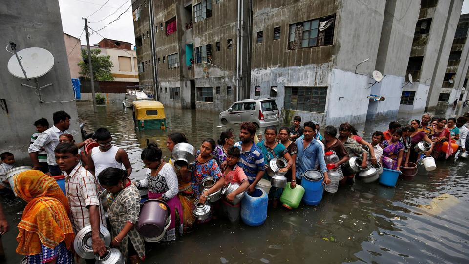 People queue to collect drinking water from a municipal tanker at a flooded residential colony in Ahmedabad. (REUTERS/Amit Dave )