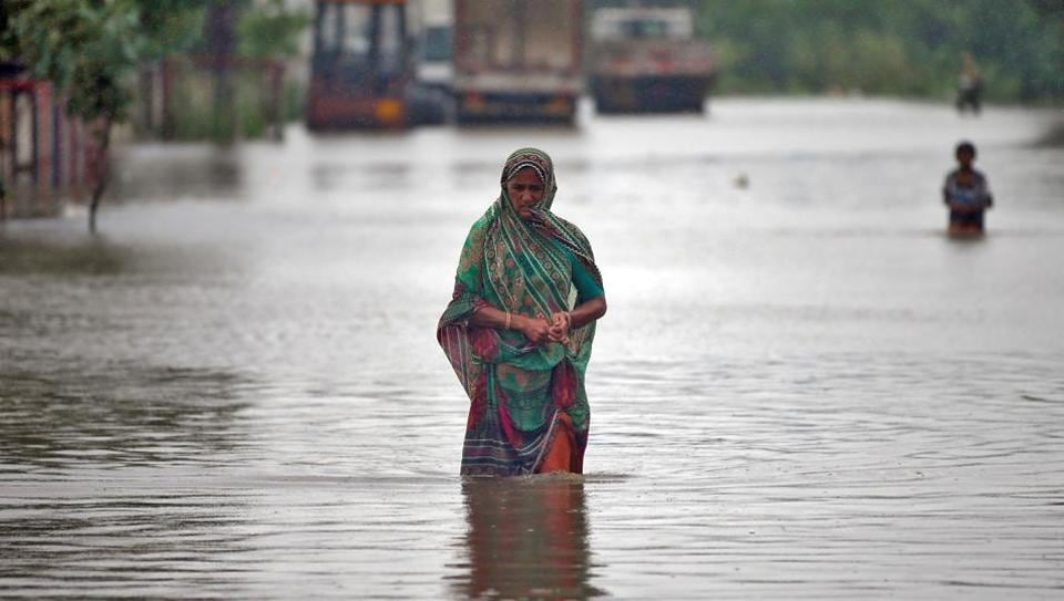 A woman wades through a road flooded by heavy rain in Ahmedabad on  July 24.  (REUTERS/Amit Dave)