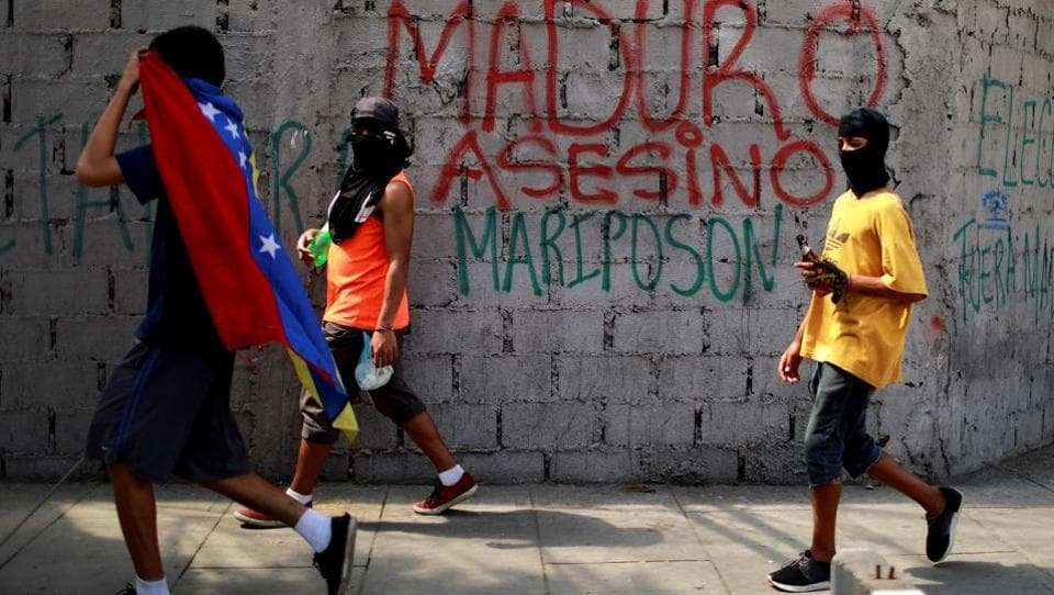 Demonstrators walk past a graffiti that reads 'Murderer Maduro' during a strike called to protest against Venezuelan President Nicolas Maduro's government in Caracas, Venezuela .  (REUTERS/Marco Bello)