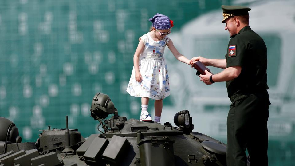 A Russian serviceman stands with a girl on top of a T-72 tank on display during the opening ceremony of the International Army Games 2017 in Alabino outside Moscow, Russia (REUTERS/Maxim Shemetov )