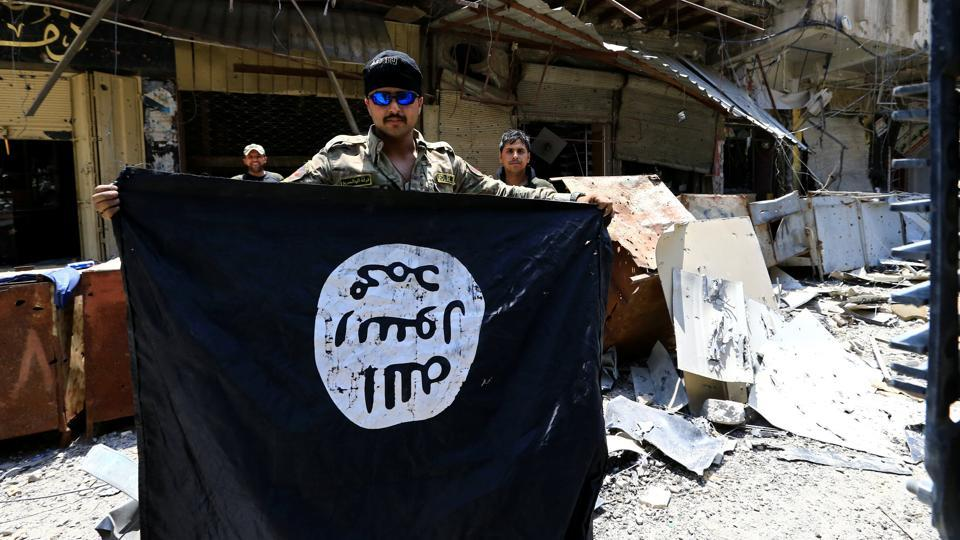 A man holds an Islamic State flag in Mosul, Iraq. Britain's officials say 850 fighters have travelled to Iraq and Syria to fight with the IS.