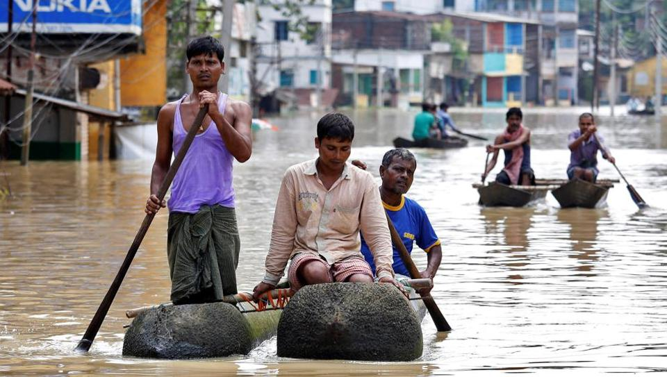 People paddle their boats as they try to move to safer places along a flooded street in West Midnapore district of West Bengal.