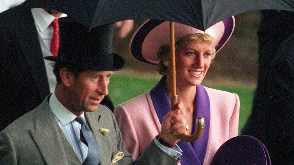 Britain's Princess Diana and Prince Charles, take shelter under an umbrella while attending the second day of the Royal Ascot horse race meet near London June 20, 1990.