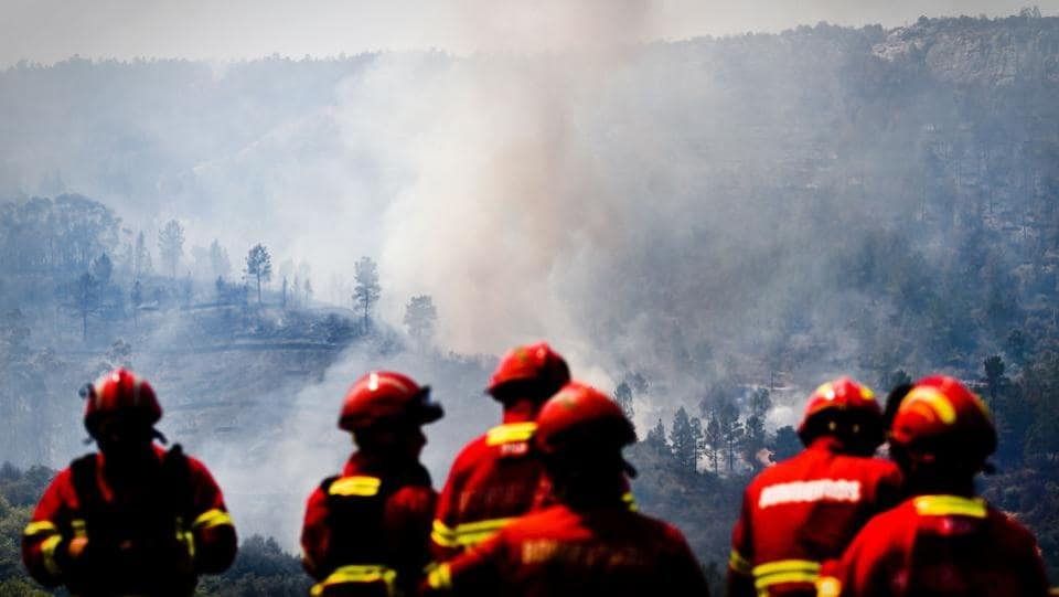 Firefighters stand on a bridge that leads to Nisa as a wildfire rages near Vila Velha de Rodao, central Portugal. Forest fires raged in the early hours of Thursday in central Portugal, cutting off roads and forcing thousands to flee just a month after deadly blazes left more than 60 people dead.  (AFP PHOTO / PATRICIA DE MELO MOREIRA)