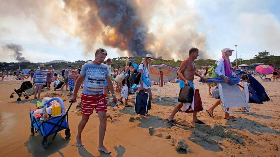 Tourists evacuate the beach as smoke fills the sky above a burning hillside in Bormes-les-Mimosas in the Var department, France.  (REUTERS/Jean-Paul Pelissie)