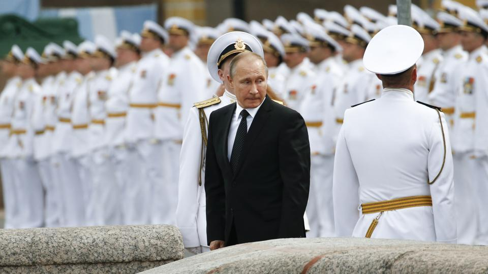 Russian sailors stand in attention as Russian President Vladimir Putin leaves after attending the military parade during the Navy Day celebration in St.Petersburg, Russia, on Sunday, July 30, 2017.
