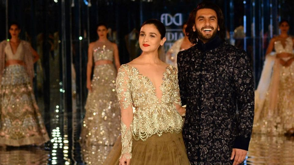 Alia Bhat and Ranveer Singh present creations by Indian fashion designer Manish Malhotra during the FDCI India Couture week 2017 in New Delhi on July 30.