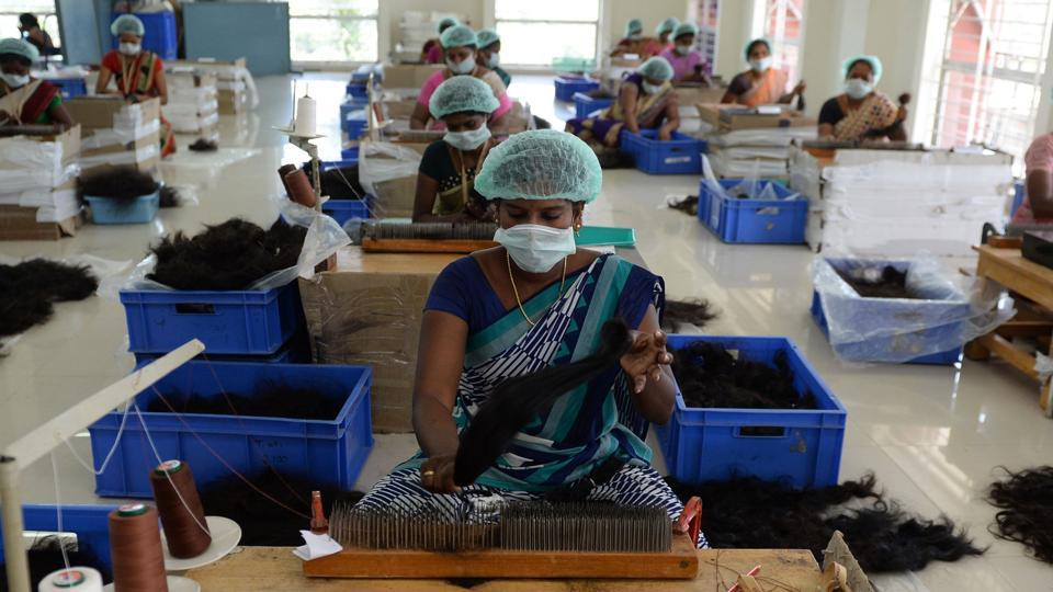 Workers at one of the hair processing plants sort and segregate hair on the basis of quality and cut. Indian hair is considered more valuable in foreign markets due to its higher quality and a lack of chemical dyes and processing done by the wearer.  (Arun Sankar / AFP)