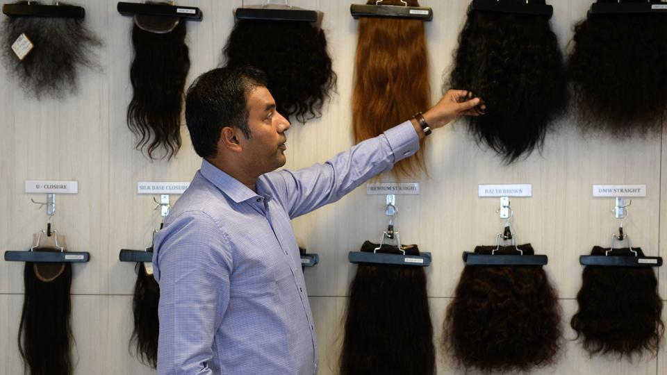 George B. Cherian, managing director of Raj Hair International, explains different hair products at the company's display centre in Chennai. While hair products manufactured from temple hair is often sold internationally, a part of the finished product also makes its way back into India, ironically branded as imported wig and extensions sourced and produced 'ethically'. (Arun Sankar / AFP)