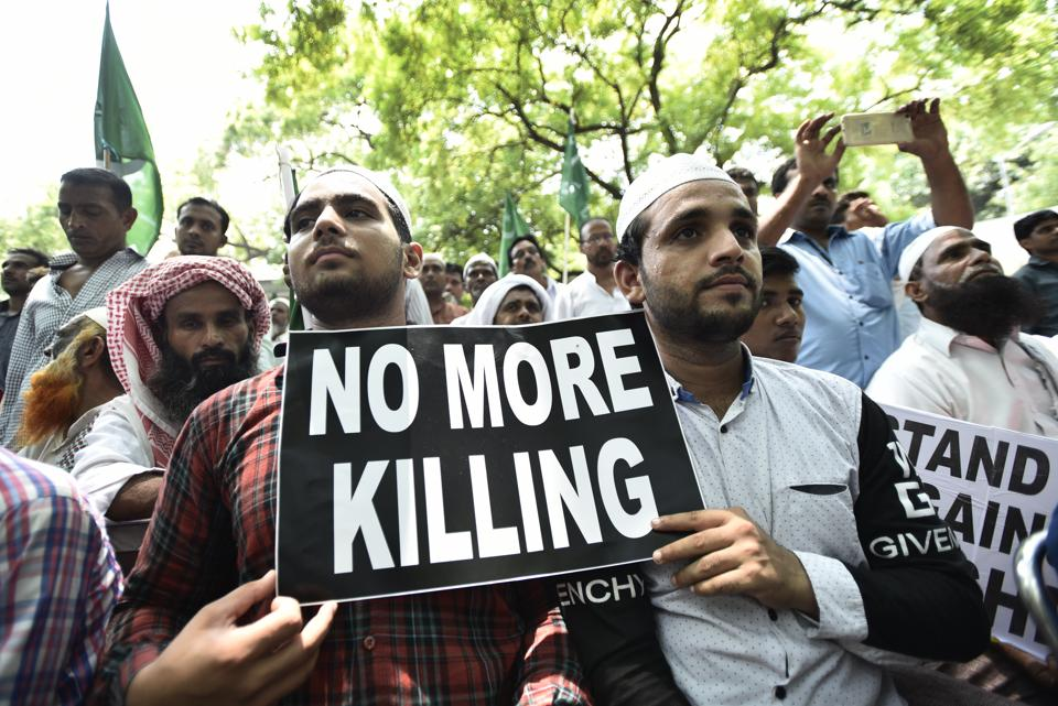 Protesters hold placards as they participate  in a sit-in over a spate of assaults against Muslims and low-caste Dalits by Hindu vigilantes, New Delhi, July 18