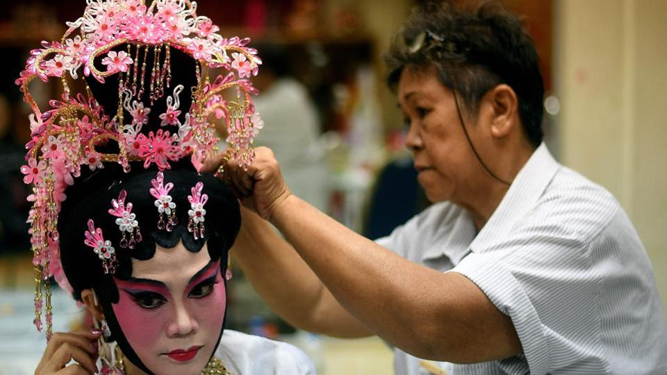 An ethnic Malaysian-Chinese Cantonese opera actress (L) from the Sound of Tai Hei group prepares backstage before an opera performance in Kuala Lumpur.  (MANAN VATSYAYANA / AFP)