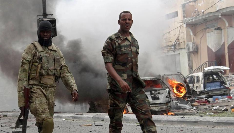 Somalian security personnel walk past burning vehicles as they secure an area in Mogadishu on July 30, 2017, after a car bomb explosion in the Somalian capital.