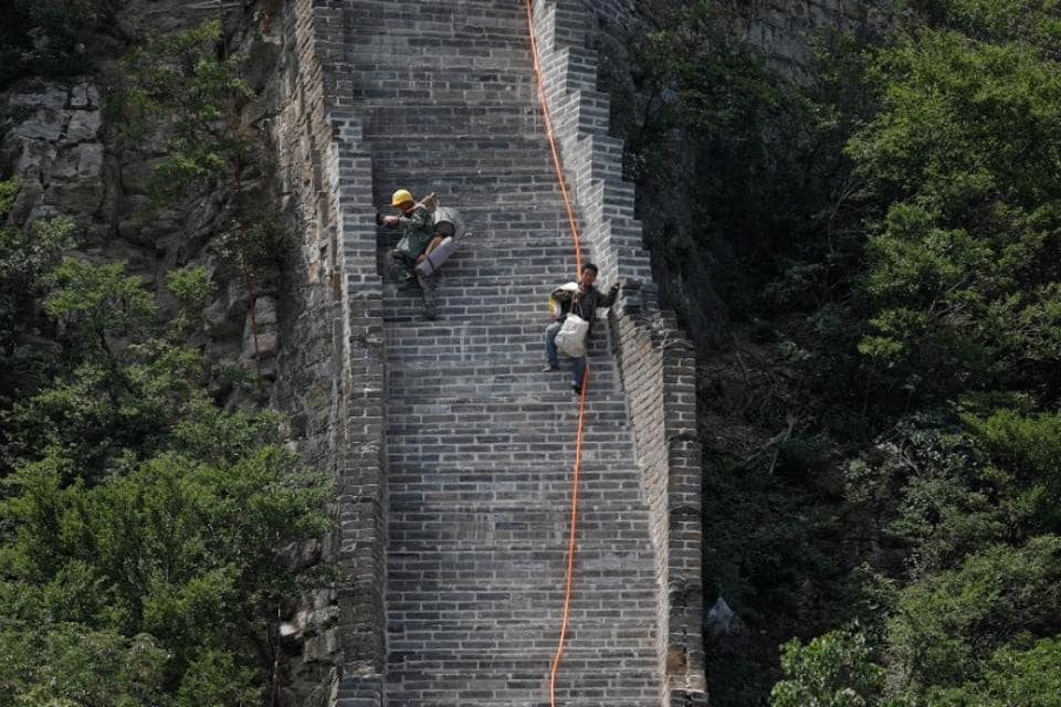 Workers carry their tools and belongings as they climb down the Jiankou section of the Great Wall, located in Huairou District, north of Beijing, China.