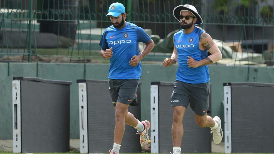 Virat Kohli and Cheteshwar Pujara warm up before a practice session at Colombo.  (AFP)