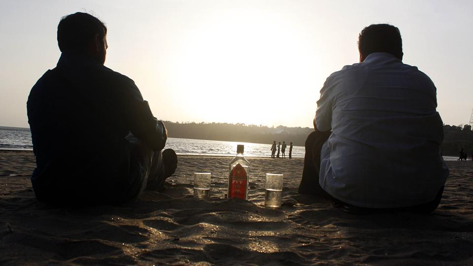 Tourists enjoy a drink of Goa's local alcoholic beverage, Feni, at Bambolim beach.