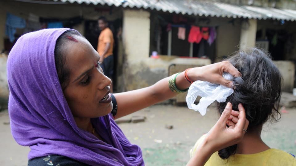 A woman shows her daughter's braids that were allegedly chopped onMonday night in Ravi Nagar, Gurgaon.