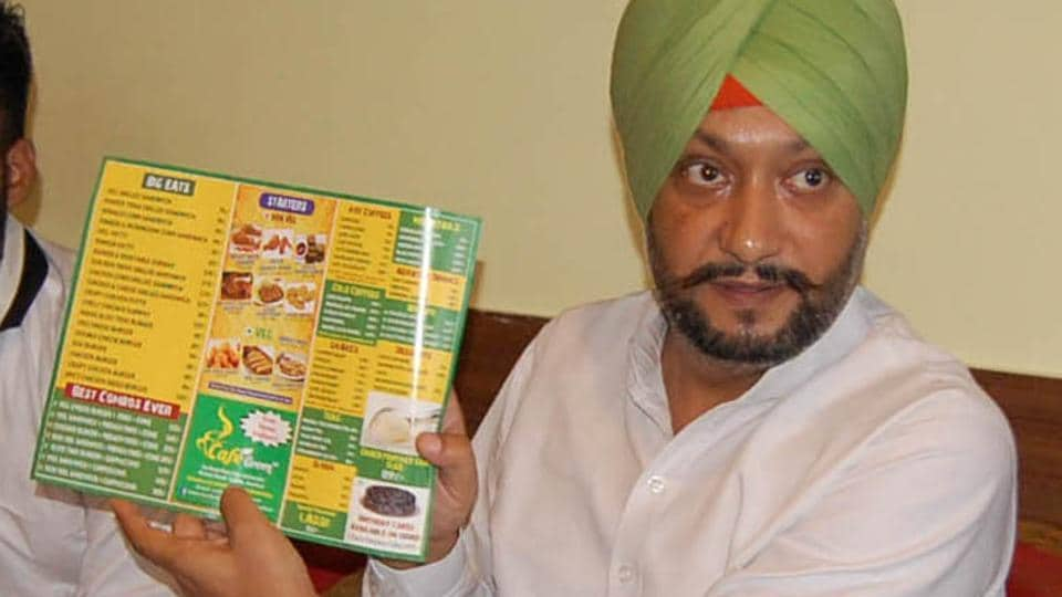 Former Congress leader Mandeep Singh Manna addressing a press conference in Amritsar on Tuesday, showing a menu card of non-veg items at a cafe run on premises of an SGPC-run medical institute.