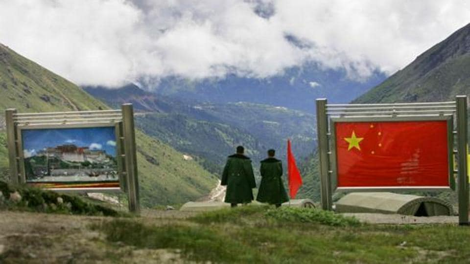 Chinese army officers oversee preparations as they stand between pictures of the Patola Palace, and the Chinese flag, on the Chinese side of the international border at Nathula Pass, in Sikkim on July 5, 2006.