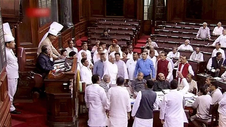 MPs of Opposition parties storm into the ell of the Rajya Sabha to protest governement's decision to hike the prices of LPG, in New Delhi on Tuesday.