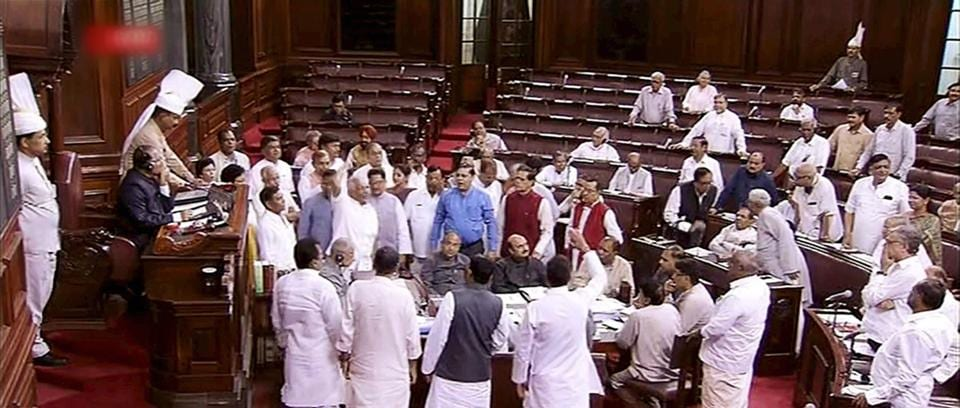 Opposition MPs storm into the Well of Rajya Sabha to protest government's decision to hike the prices of LPG cylinder, in New Delhi on Tuesday.