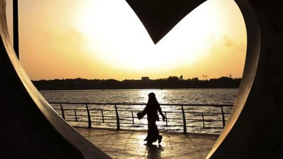 A Saudi woman seen through a heart-shaped statue walks along an inlet of the Red Sea in Jeddah, Saudi Arabia.