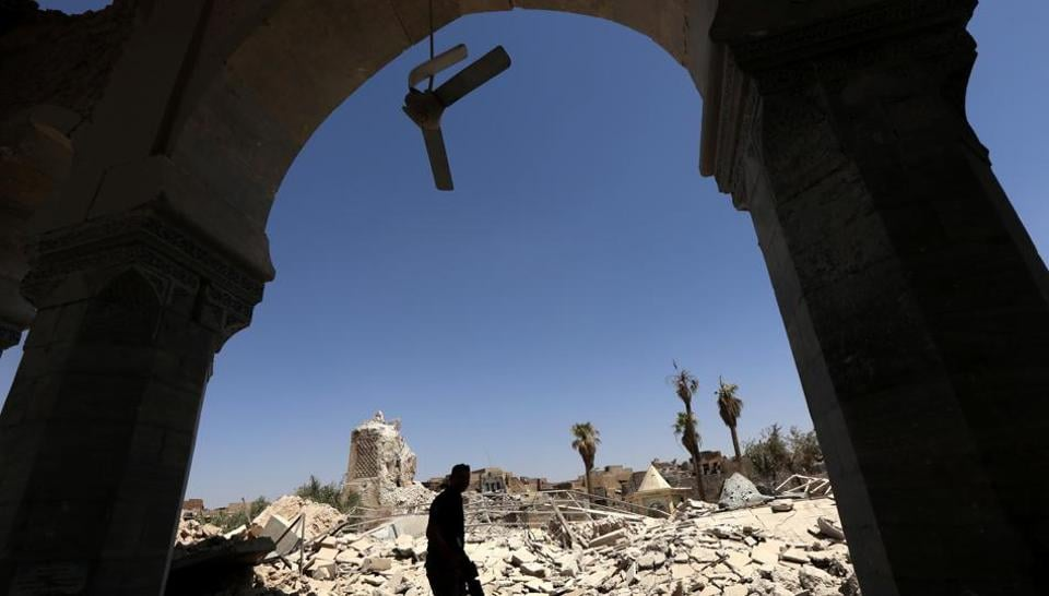 A member of Iraq's Counter-Terrorism Service walks in the rubble near the destroyed ancient leaning minaret, known as the