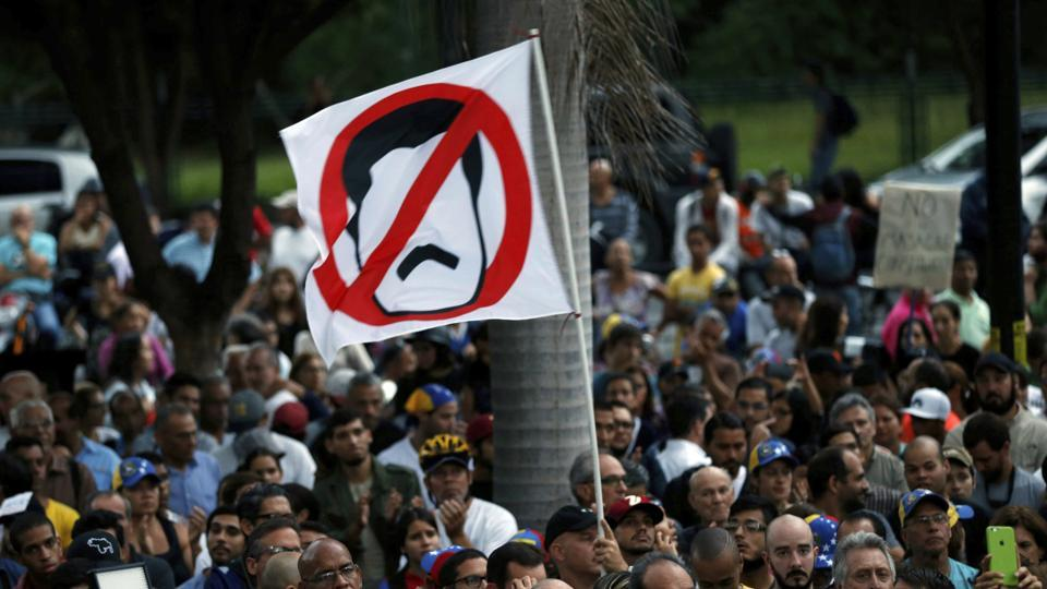 An anti-government demonstrator waves a flag against Venezuela's President Nicolas Maduro during a vigil in honour of those who have been killed during clashes between security forces and demonstrators in Caracas, Venezuela.