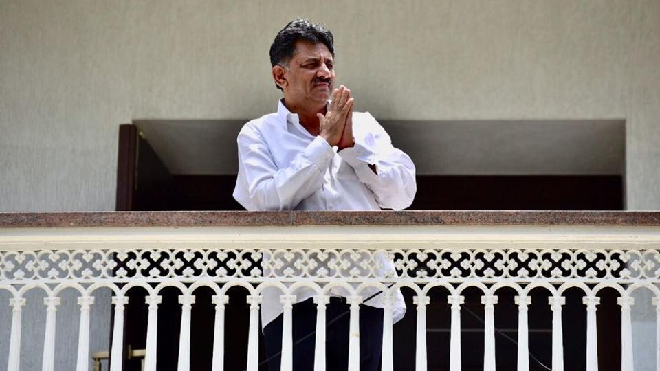 DK Shivakumar gestures to the media from his residence in Bengaluru.
