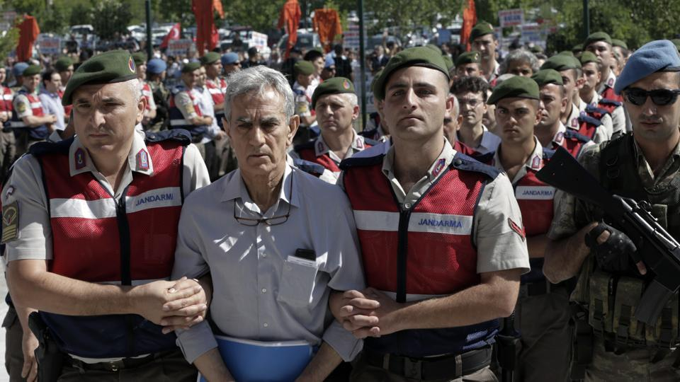 Paramilitary police and special force members escort Akin Ozturk, former Air Force commander, outside the courthouse as nearly 500 suspects, including a number of generals and military pilots, accused of leading last year's failed coup attempt and carrying out attacks from an air base in Ankara, arrive for trial in Ankara, Turkey, Tuesday.