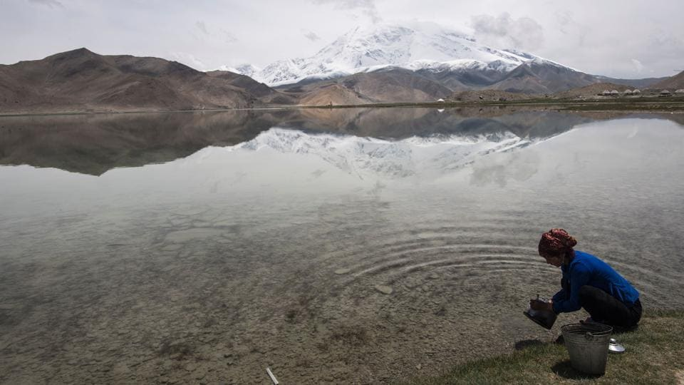 A woman collecting water from the Karakul Lake before the Karakorum mountain range next to the China-Pakistan Friendship Highway, near Tashkurgan. The remote town of around 9,000 is at the geographic heart of Beijing's plans to build a major trade artery – the China-Pakistan Economic Corridor (CPEC) — connecting Kashgar to the Arabian Sea port of Gwadar. (Johannes EISELE / AFP)