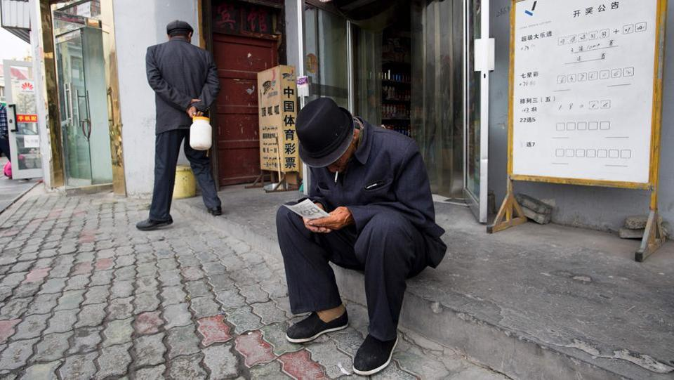 A man looking at his lottery ticket in Tashkurgan, China's western Xinjiang province.  India  has boycotted the Belt and Road Intiative, mainly due to concerns over the China-Pakistan Economic Corridor, a key part of the initiative that runs through disputed Kashmir. (Johannes EISELE / AFP)