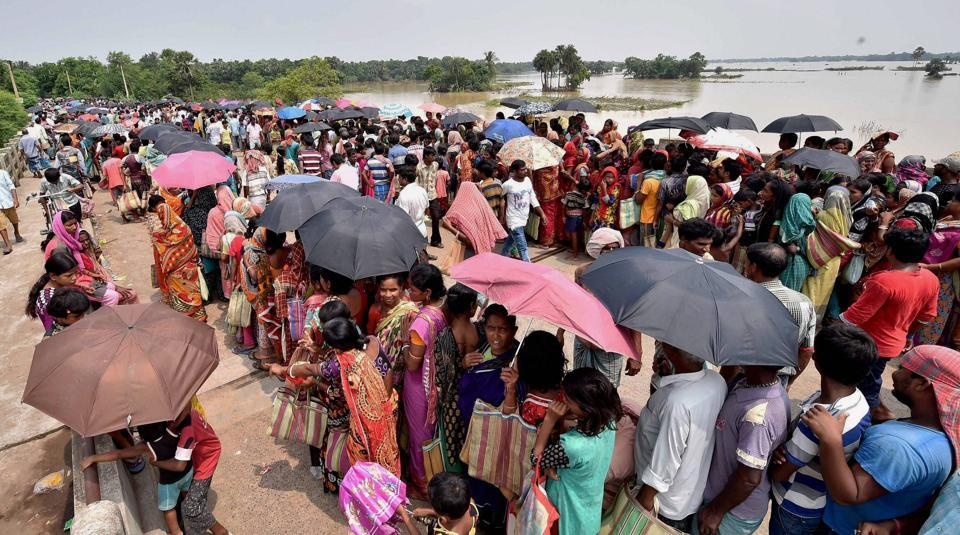Flood victims stand in a queue while waiting for relief material at Dhanyaghari Village, Amta II of Howrah district on August 2, 2017.