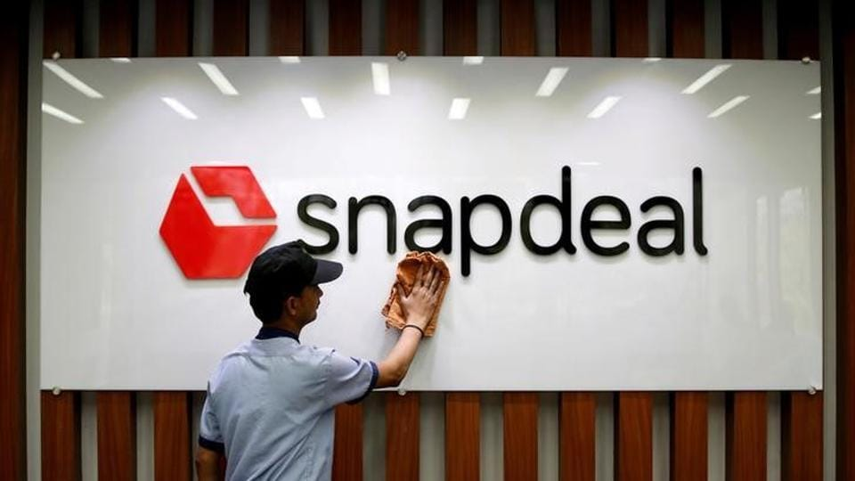 An employee cleans a Snapdeal logo at its headquarters in Gurugram on the outskirts of New Delhi on April 3.