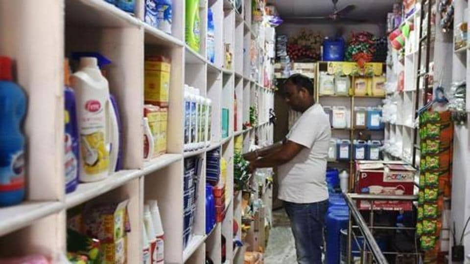 A shopkeeper arranges goods on a shelf inside his shop in New Delhi.