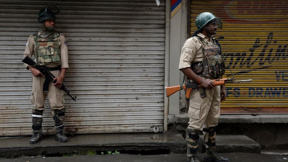 Paramilitary troopers stand guard during restrictions after Kashmiri separatists called for a one-day strike to protest a civilian killing in Srinagar on August 2, 2017.