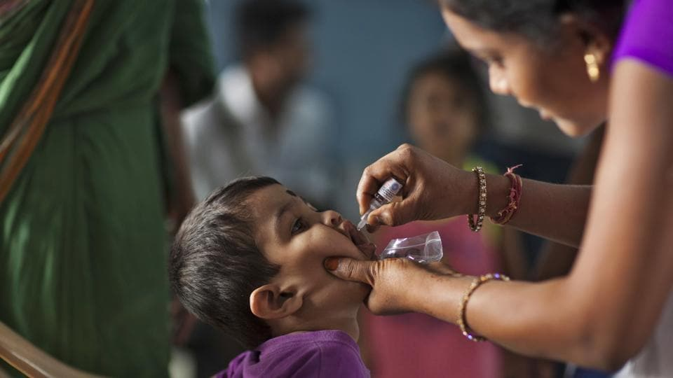 A medical volunteer administers a dose of polio immunisation to a child in Hyderabad.