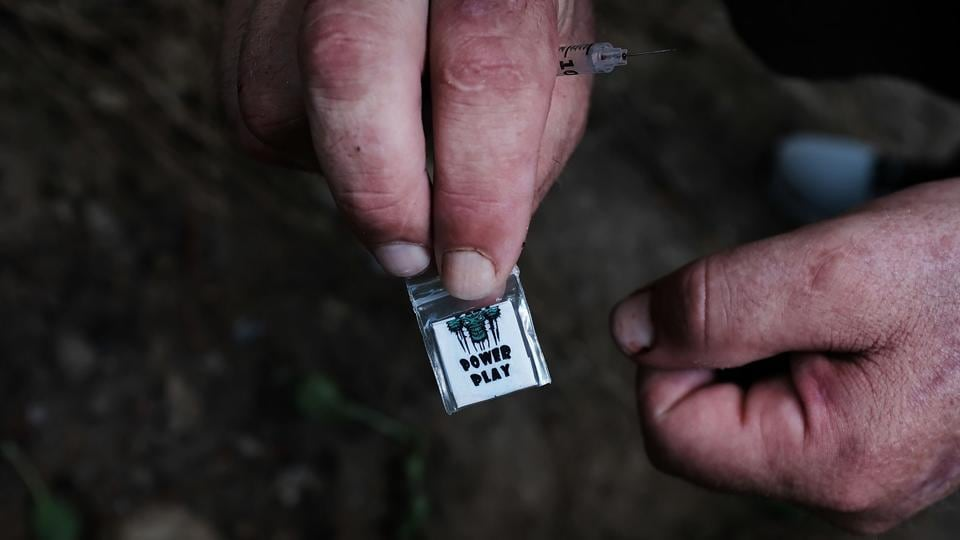 Chris, a homeless heroin addict displays a brand of heroin called 'power play' available on the streets for $5. The report also sheds light on the fact that four out of every five eventual heroin users begin with non medical use of prescription pills. (Spencer Platt / Getty Images / AFP)