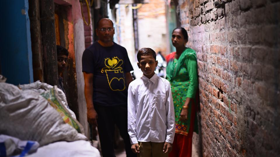 Sonu with his parents outside his house in east Delhi's New Seemapuri. He started going to a formal school on July 10 this year.