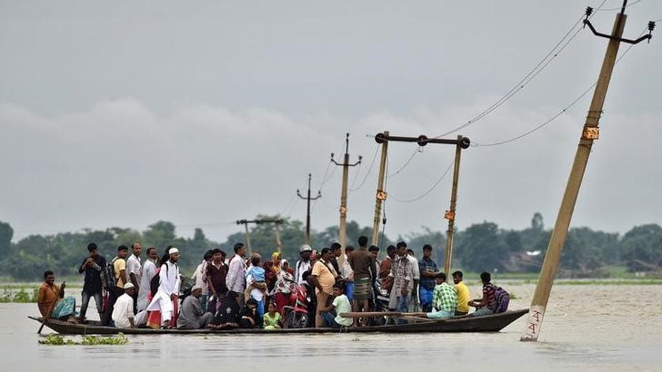 Villagers use a boat to cross a flooded road at Asigarh village in Morigaon district in Assam.