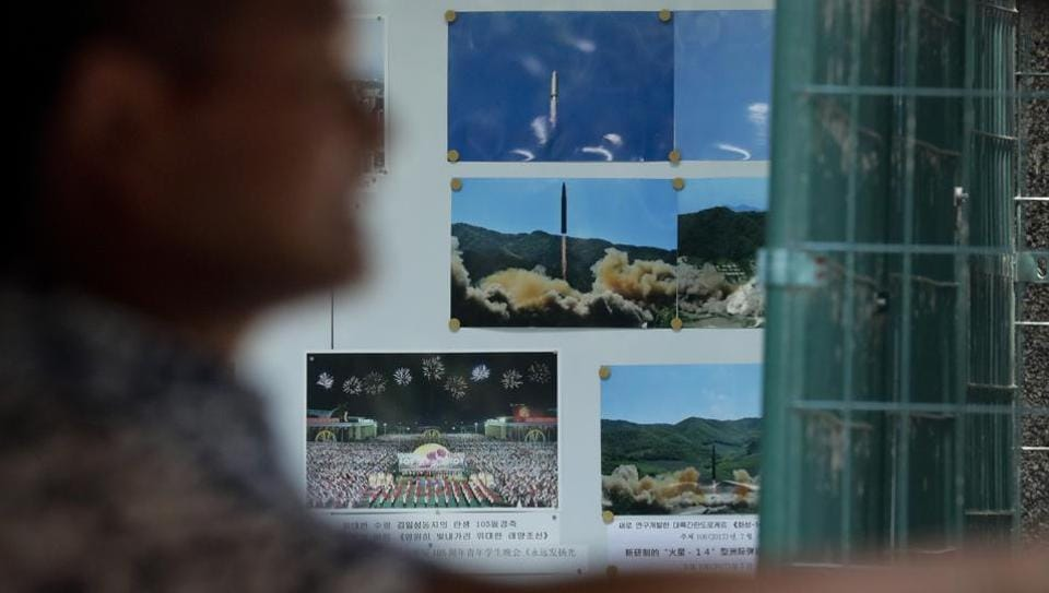 A man drives his car past a display board showing photos of ballistic missile launches in North Korea outside the North Korean Embassy in Beijing on August 3.