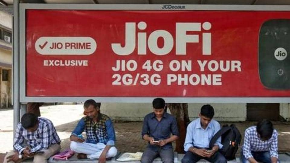 Commuters use their mobile phones as they wait at a bus stop with an advertisement of Reliance Industries' Jio telecoms unit, in Mumbai.
