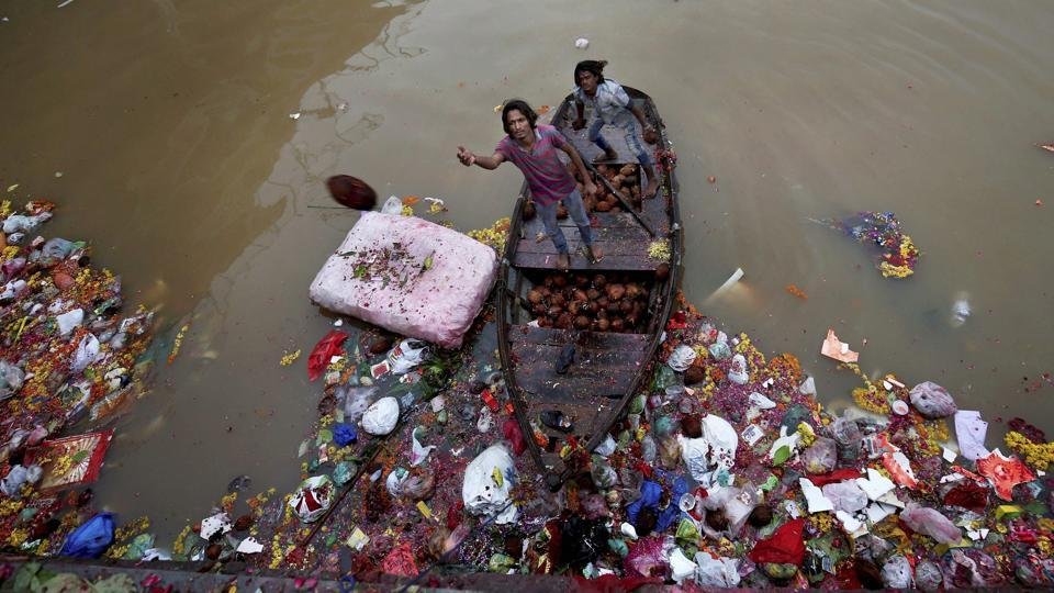Men wade through religious offerings and immersed idols by the bank of the Sabarmati  river which cuts through Ahmedabad, to collect coconuts and other reusables thrown by devotees. (PTI)