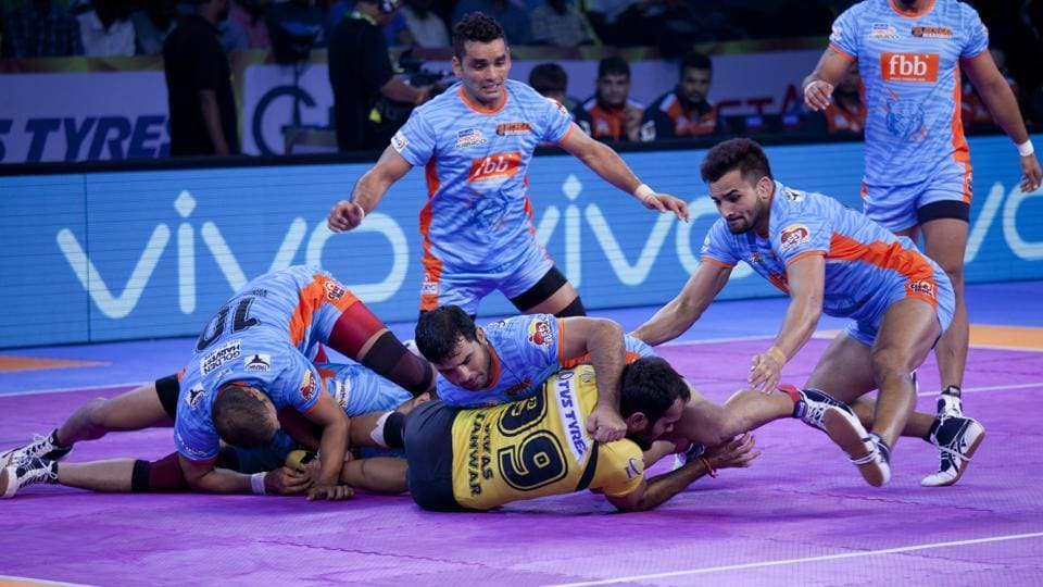 Bengal Warriors players pin down Telugu Titans' Vikas, in yellow jersey, during their Pro Kabaddi League match.