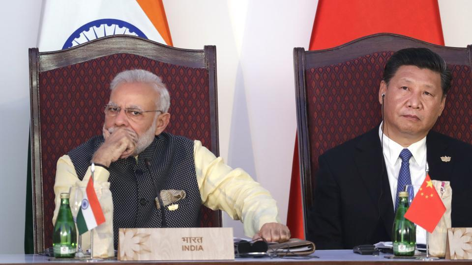 FILE - In this Oct. 16, 2016, file photo, Indian Prime Minister Narendra Modi, left, and Chinese President Xi Jinping listen to a speech during the BRICS Leaders Meeting with the BRICS Business Council in Goa, India.