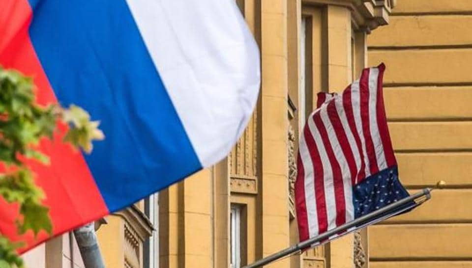 A Russian flag flies next to the US embassy building in Moscow on July 31, 2017. President Vladimir Putin on July 30, 2017 said the United States would have to cut 755 diplomatic staff in Russia and warned of a prolonged gridlock in its ties after the US Congress backed new sanctions against the Kremlin.