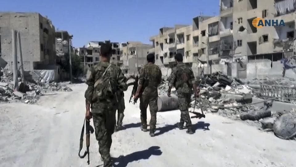 This frame grab from video released Thursday August 3, 2017 and provided by Hawar News Agency, a Syrian Kurdish activist-run media group, shows US-backed Syrian Democratic Forces (SDF) fighters patrolling on a street in the northern city of Raqqa, Syria.