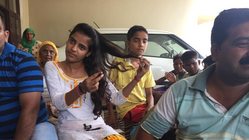 18-year-old Shikha shows where her hair was cut.