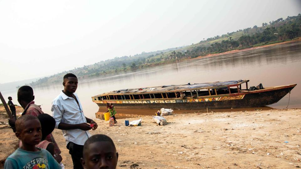 People standing next to an empty boat as the traffic on the Kasai river has been slowed down due to insecurity at the port of Tshikapa, Democratic Republic of Congo.