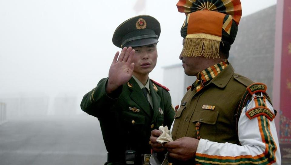 A Chinese soldier and an Indian soldier at the Nathu La border crossing between India and China in Sikkim. A border standoff has heightened tension between the two neighbours.